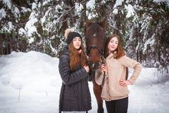 Hermanas y caballo gemelos en el bosque del invierno Fotografía de archivo