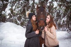 Hermanas y caballo gemelos en el bosque del invierno Imagen de archivo