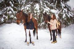 Hermanas y caballo gemelos en el bosque del invierno Imágenes de archivo libres de regalías