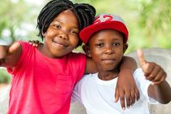 Hermano africano y hermana que hacen los pulgares para arriba Imagenes de archivo