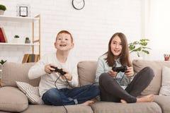 Hermano amistoso y hermana que juegan a los videojuegos juntos imagenes de archivo