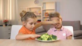 Hermano de alimentación de la pequeña hermana con el bróculi que cubre sus ojos, amigo humorístico metrajes