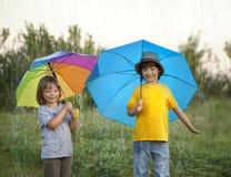 Hermano feliz con el paraguas al aire libre Fotos de archivo