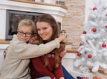 Hermano feliz que abraza a su hermana cerca de un árbol de navidad Fotos de archivo libres de regalías