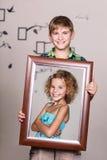 Hermano feliz que sostiene el retrato con su hermana Fotos de archivo