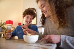 Hermano feliz y hermana que comen la comida Imagen de archivo libre de regalías
