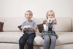Hermano feliz y hermana que juegan al videojuego en el sofá Imagen de archivo libre de regalías