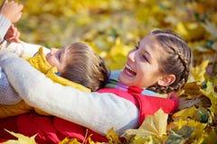 Hermano feliz y hermana que juegan en el parque Imágenes de archivo libres de regalías