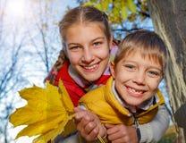 Hermano feliz y hermana que juegan en el parque Imagenes de archivo