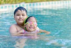 Hermano feliz y hermana que juegan en piscina imágenes de archivo libres de regalías