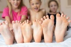 Hermano feliz y hermanas que se sientan en la cama descalzo fotografía de archivo