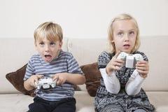 Hermano joven y hermana que juegan al videojuego Imagenes de archivo
