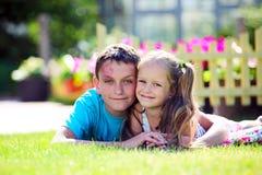 Hermano lindo y hermana que mienten en la hierba Imagen de archivo