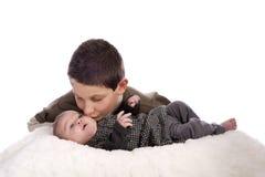 Hermano mayor que da un beso en esta hermana del bebé Foto de archivo libre de regalías