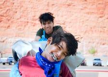 Hermano mayor que empuja al muchacho discapacitado feliz en silla de ruedas Fotos de archivo