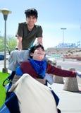 Hermano mayor que empuja al muchacho discapacitado feliz en silla de ruedas Imagen de archivo libre de regalías