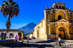 Hermano Pedro church & Agua volcano, Antigua, Guatemala. Hermano Pedro church, Antigua, Guatemala - Oct 5, 2014: Typical street scene in Spanish colonial town of stock photos