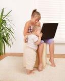 Hermano que mira en la computadora portátil Foto de archivo libre de regalías