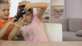 Hermano que perturba de la niña que juega al juego de la consola, niños que luchan la palanca de mando metrajes