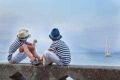 Hermano similar dos que se sienta en la costa, fotos de archivo