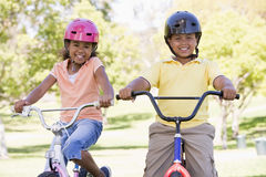 Hermano y hermana al aire libre al sonreír de las bicicletas Fotos de archivo libres de regalías