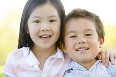 Hermano y hermana al aire libre que sonríen imagen de archivo libre de regalías