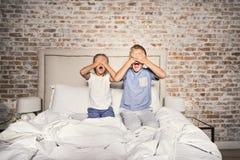 Hermano y hermana asustados en dormitorio imagenes de archivo