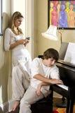 Hermano y hermana del adolescente en el país por el piano Imagenes de archivo