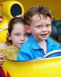 Hermano y hermana en coche de carreras Imágenes de archivo libres de regalías