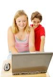 Hermano y hermana en el ordenador Imágenes de archivo libres de regalías