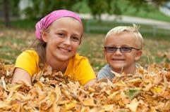 Hermano y hermana en hojas de otoño Fotos de archivo libres de regalías
