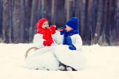 Hermano y hermana felices en el muñeco de nieve de los trajes que camina en bosque del invierno Imágenes de archivo libres de regalías