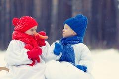 Hermano y hermana felices en el muñeco de nieve de los trajes que camina en bosque del invierno Fotos de archivo libres de regalías