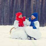 Hermano y hermana felices en el muñeco de nieve de los trajes que camina en bosque del invierno Foto de archivo libre de regalías