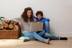 Hermano y hermana felices que usa el ordenador portátil junto Fotografía de archivo libre de regalías
