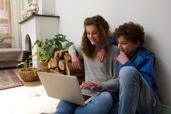 Hermano y hermana felices que usa el ordenador portátil junto en casa Imagen de archivo
