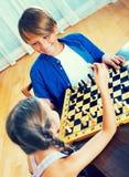 Hermano y hermana que juegan a ajedrez Foto de archivo
