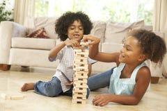 Hermano y hermana que juegan al juego en el país Foto de archivo
