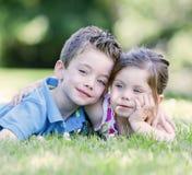 Hermano y hermana que ponen en la hierba Imagen de archivo