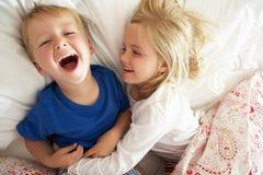 Hermano y hermana que se relajan junto en cama imágenes de archivo libres de regalías