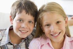 Hermano y hermana que se sientan de lado a lado en un sofá Imagenes de archivo
