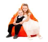 Hermano y hermana que se sientan en una silla Foto de archivo