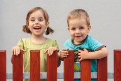Hermano y hermana que sonríen detrás de la cerca Foto de archivo libre de regalías