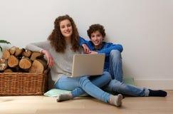 Hermano y hermana sonrientes que usa el ordenador portátil en casa Fotografía de archivo