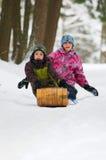 Hermano y hermana tobogganing Imagen de archivo