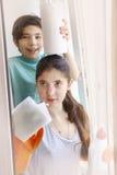 Hermanos adolescentes muchacha y muchacho en los guantes de goma anaranjados que limpian la ventana Fotos de archivo