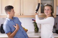 Hermanos adolescentes que tienen lucha en cocina Fotos de archivo libres de regalías
