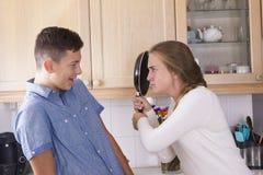 Hermanos adolescentes que tienen lucha en cocina Imágenes de archivo libres de regalías