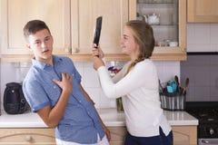 Hermanos adolescentes que tienen lucha en cocina Fotografía de archivo libre de regalías