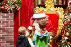 Hermanos agradables que hablan con Santa Claus en área internacional de la impulsión imagen de archivo